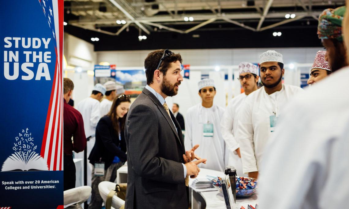 Embassy man talking to group of Omani men at USA booth at education fair