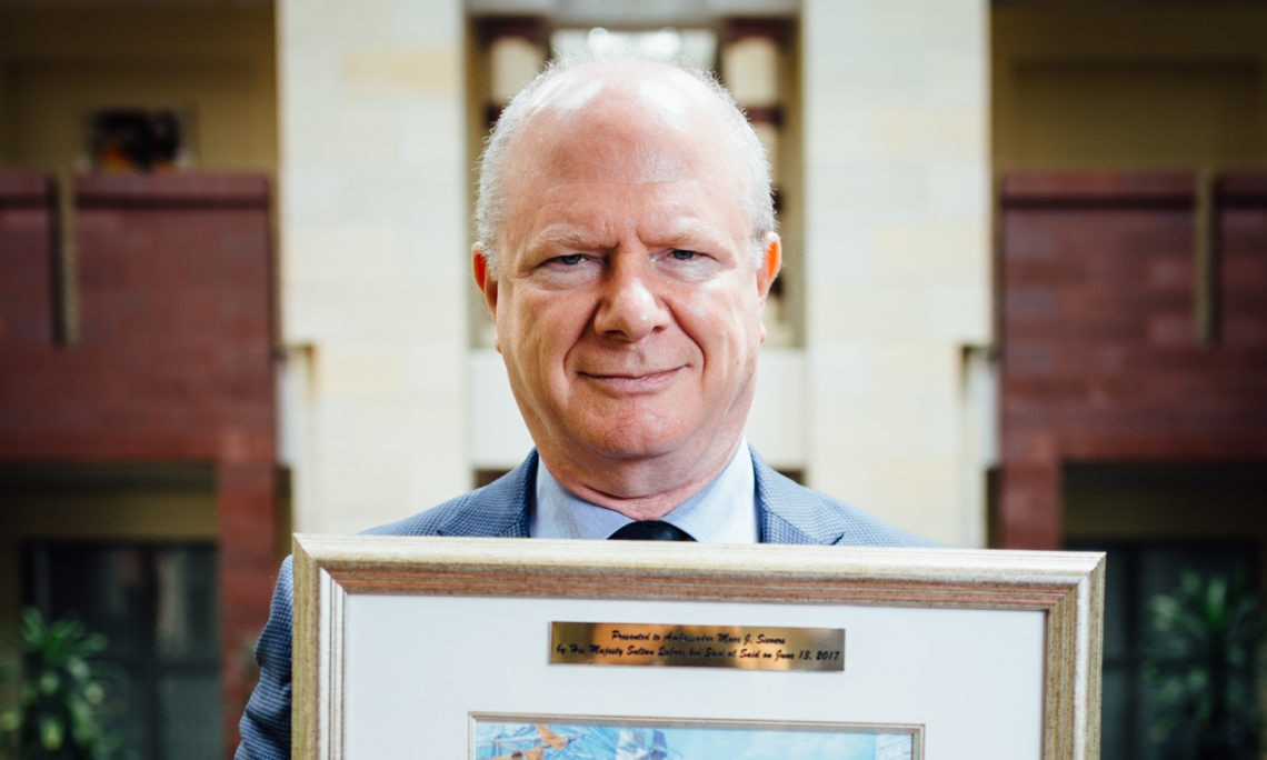 U.S. Ambassador Marc J. Sievers holding a gift from Sultan Qaboos.